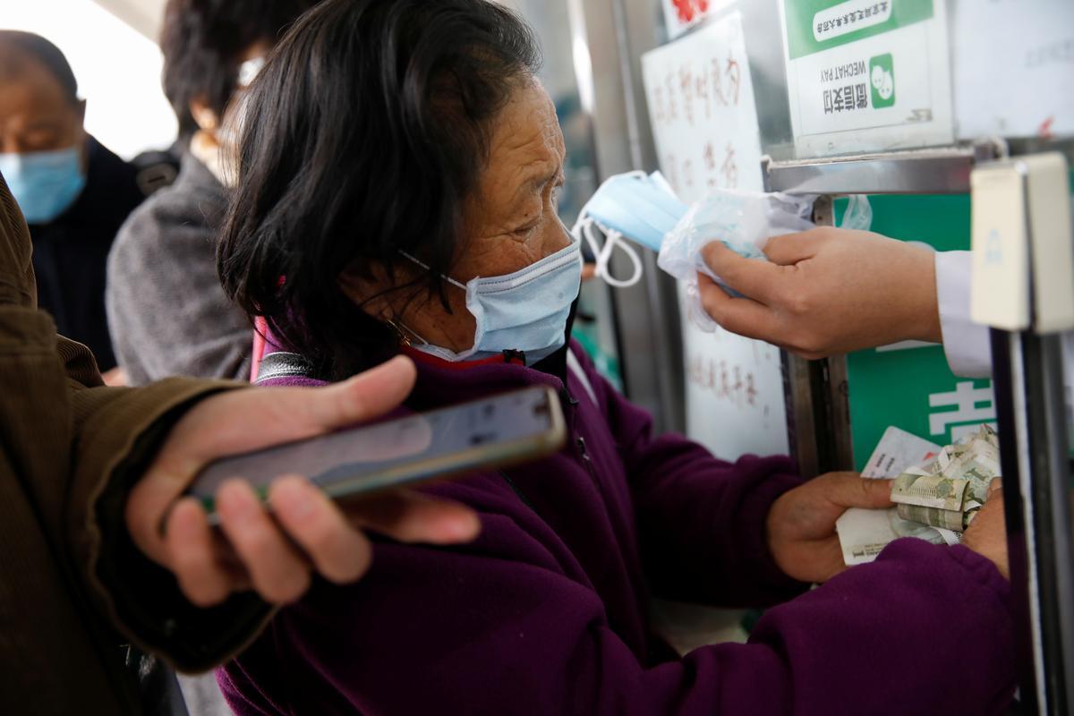 China posts sharp drop in new coronavirus cases after criteria change