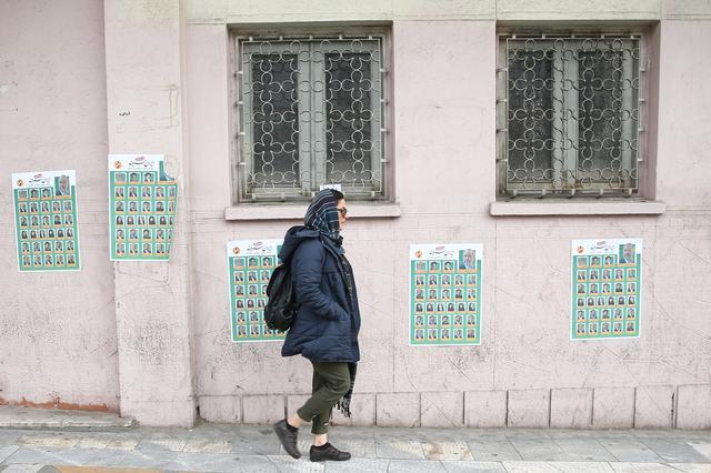 A woman walks past parliamentary election campaign posters in Tehran, Iran February 19, 2020. WANA (West Asia News Agency)/Nazanin Tabatabaee via REUTERS