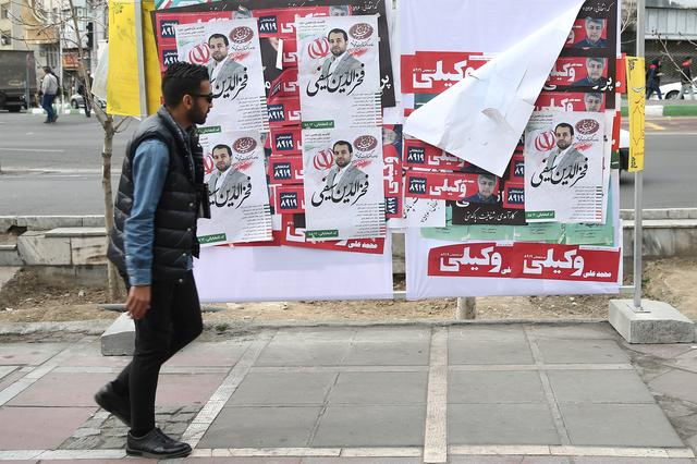 A man walks past parliamentary election campaign posters in Tehran, Iran February 19, 2020. WANA (West Asia News Agency)/Nazanin Tabatabaee via REUTERS
