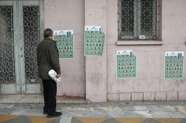 A man looks at parliamentary election campaign posters in Tehran, Iran February 19, 2020. WANA (West Asia News Agency)/Nazanin Tabatabaee via REUTERS