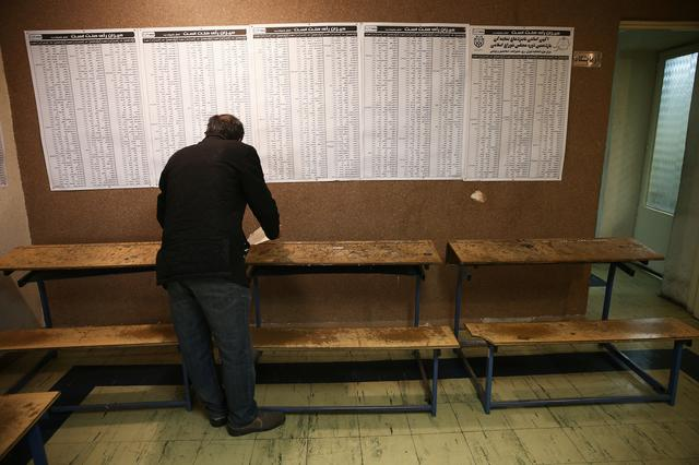 An Iranian checks the names of candidates during parliamentary elections at a polling station in Tehran, Iran February 21, 2020. Nazanin Tabatabaee/WANA (West Asia News Agency) via REUTERS