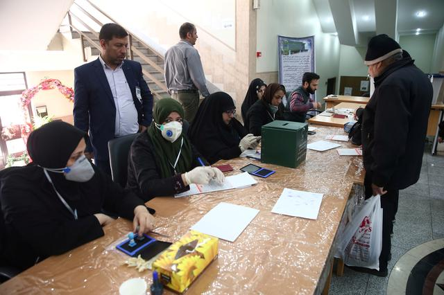 Poll workers wear face masks during parliamentary elections at a polling station in Tehran, Iran February 21, 2020. Nazanin Tabatabaee/WANA (West Asia News Agency) via REUTERS