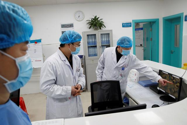 FILE PHOTO: Doctors look at a screen that shows the ward where patients who are infected with the coronavirus are treated at the First People's Hospital in Yueyang, Hunan Province, near the border to Hubei Province, which is under partial lockdown after an outbreak of a new coronavirus, in China January 28, 2020.  REUTERS/Thomas Peter