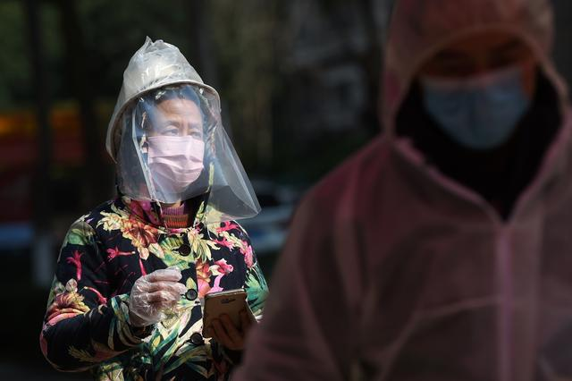 A resident wearing makeshift protective face shield waits to collect food and necessities purchased through group orders at an entrance to a residential compound in Wuhan, the epicentre of the novel coronavirus outbreak, Hubei province, China February 21, 2020. REUTERS/Stringer