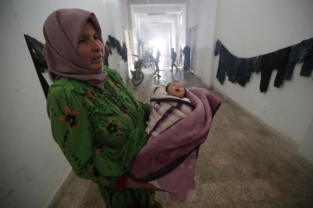 Hayat al-Fayad, 50, carries her granddaughter, at an empty school and university compound used as shelter, in Azaz, Syria February 21, 2020.  REUTERS/Khalil Ashawi