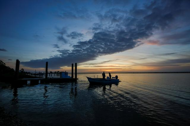 Michael Dasher, Sr., and son Michael Dasher, Jr., both of Eastpoint, Florida, U.S., leave in their boat before dawn for a day of work harvesting oysters from Apalachicola Bay, February 11, 2020.   REUTERS/Colin Hackley