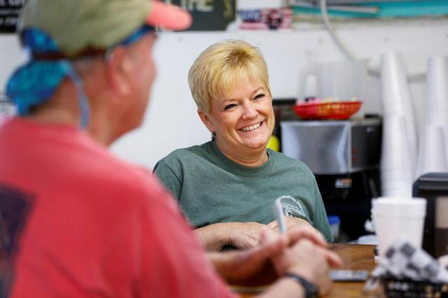Lynn Martina, owner of Lynn's Quality Oysters in Eastpoint, Florida, U.S., talks to customers in her restaurant, which often has to serve oysters from out of state due to the limited oyster production in Apalachicola Bay, February 11, 2020.   REUTERS/Colin Hackley