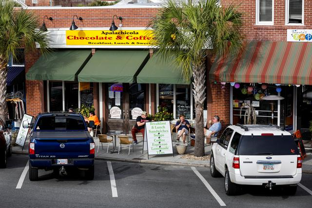 Patrons enjoy the day outside the Apalachicola Chocolate and Coffee Company in Apalachicola, Florida, U.S. February 11, 2020. REUTERS/Colin Hackley