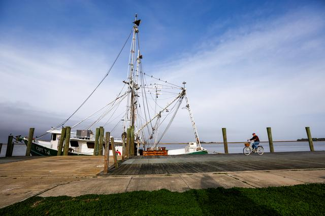 A man bicycles past the shrimp boat ''Capt. T.J.'' owned by the 13 Mile Seafood company while it is docked in Apalachicola, Florida, U.S. February 11, 2020. REUTERS/Colin Hackley