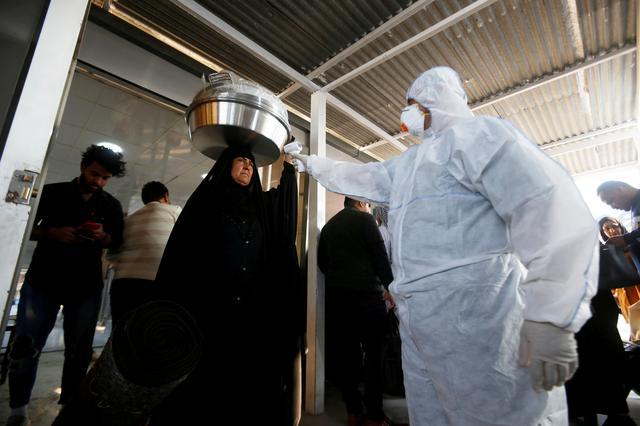 An Iraqi medical staff member checks a passenger's temperature, amid the new coronavirus outbreak, upon her arrival to Shalamcha Border Crossing between Iraq and Iran, February 20, 2020. REUTERS/Essam al-Sudani