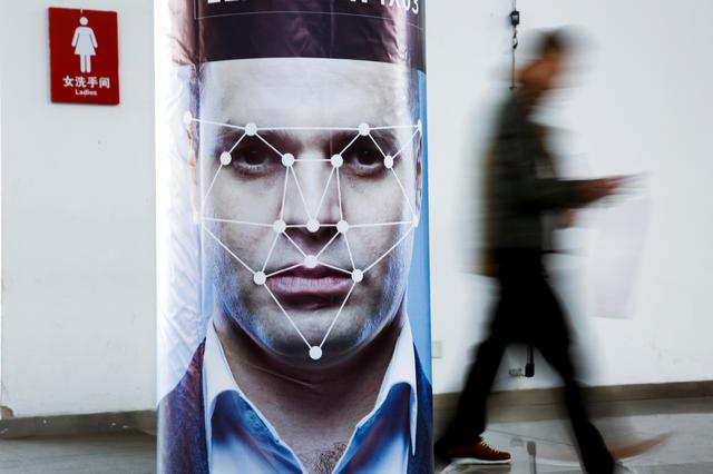 FILE PHOTO: A man walks past a poster simulating facial recognition software at the Security China 2018 exhibition on public safety and security in Beijing, China October 24, 2018.   REUTERS/Thomas Peter/File Photo