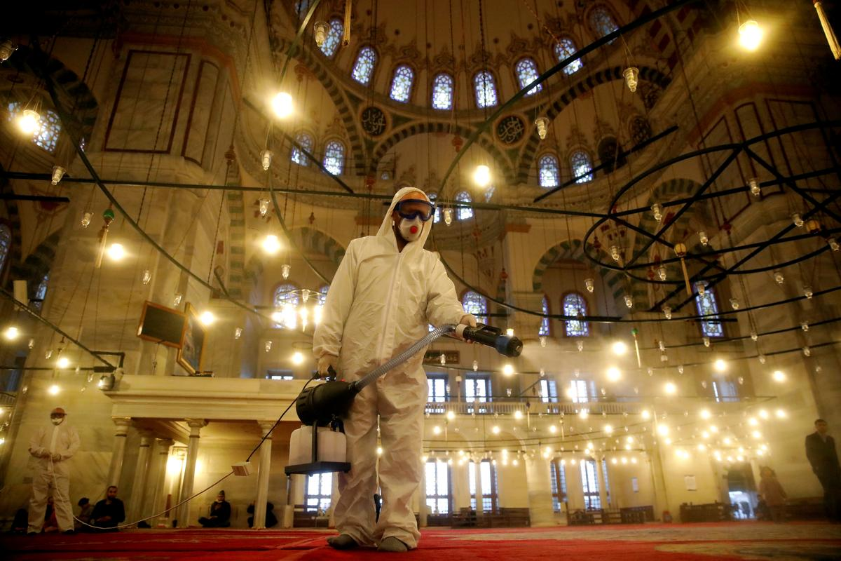 A worker in a protective suit disinfects the Fatih Mosque in Istanbul, Turkey