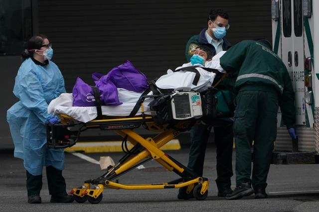 Paramedics move a patient into the hospital during the outbreak of coronavirus disease (COVID-19), in the Manhattan borough of New York City, New York, U.S., March 25, 2020. REUTERS/Carlo Allegri