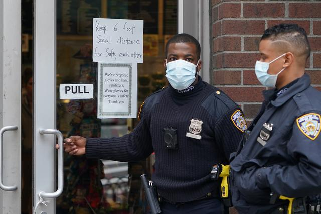 Officials walk into a store that has a ''Social Distancing'' sign on the door during the outbreak of coronavirus disease (COVID-19), in the Manhattan borough of New York City, New York, U.S., March 25, 2020. REUTERS/Carlo Allegri