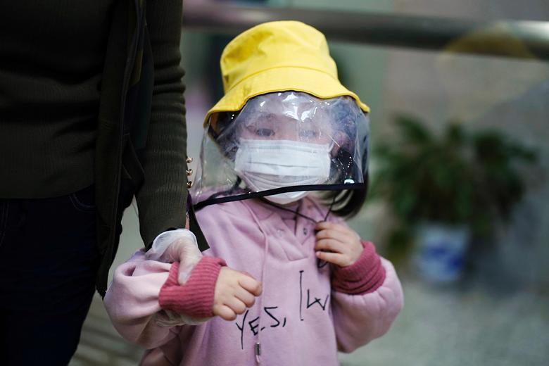 Ребенок, носящий маску и маску, замечен на железнодорожной станции в Сяньнине провинции Хубэй, Китай, 25 марта 2020 года. REUTERS / Aly Song