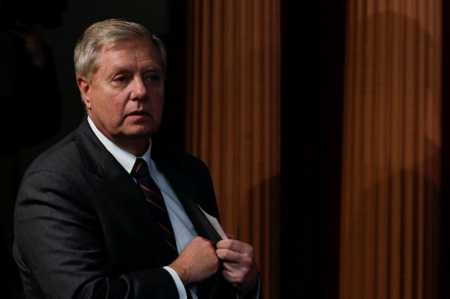 Senator Lindsey Graham (R-SC) discards his note card before delivering remarks during a news conference on the coronavirus relief bill, on Capitol Hill in Washington, U.S., March 25, 2020. REUTERS/Tom Brenner