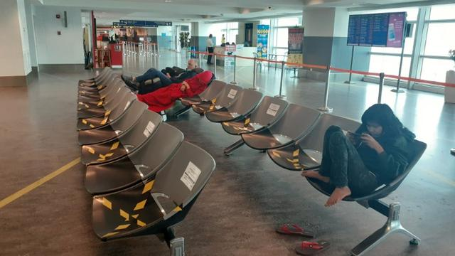 Stranded tourists sit in chairs at the transit area of Kuala Lumpur International Airport Terminal 2, after they were returned from Thailand due to new health certificate requirements amid coronavirus disease (COVID-19) epidemic, in Sepang, Selangor State, Malaysia March 24, 2020.Valarie Astashova/Handout via REUTERS