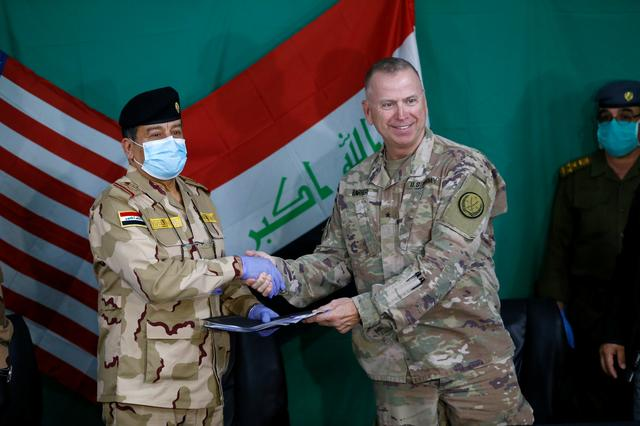 U.S. Brigadier General Vincent Barker shakes hands with Iraqi General Mohammed Fadel during the hand over of US-led coalition forces to Iraqi Security Forces at Qayyarah Airfield West in the south of Mosul, Iraq March 26, 2020. REUTERS/Thaier al-Sudani
