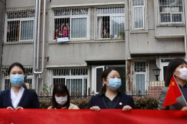 FILE PHOTO: Residents bid farewell from their homes to a medical team from Guizhou province who is leaving Wuhan, following the novel coronavirus disease (COVID-19) outbreak, in Hubei province, China March 25, 2020. China Daily via REUTERS