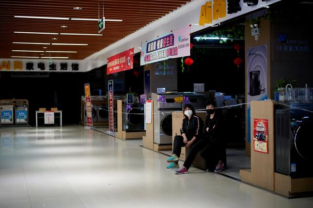 FILE PHOTO: Staff members wearing face masks sit at an electrical appliances store in Xianning of Hubei province, the epicentre of China's coronavirus disease (COVID-19) outbreak, March 25, 2020. REUTERS/Aly Song