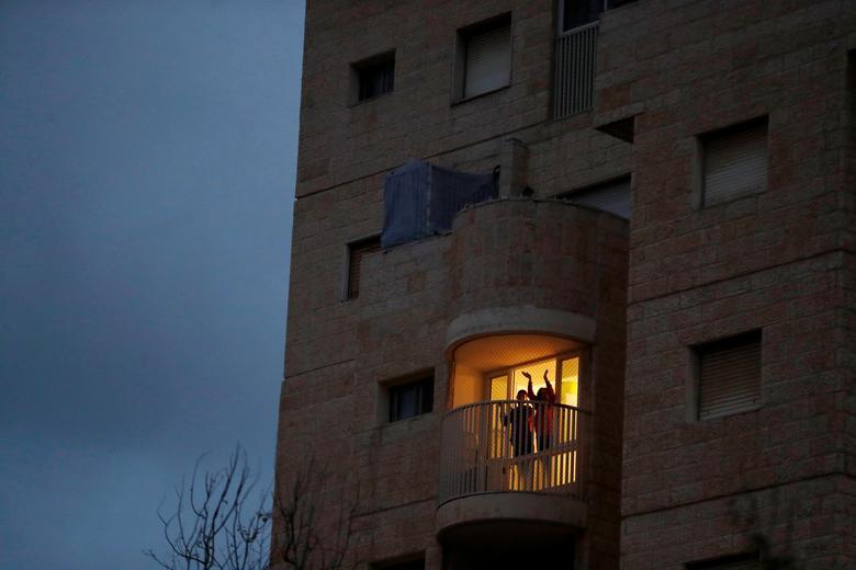 Люди стоять на балконі і плескають у долоні, беручи участь в ініціативі щодо масовим оплесків медичних бригад, що борються зі спалахом коронавируса, в Модіїна, Ізраїль, 19 березня 2020 року. РЕЙТЕР / Ронен Звулун