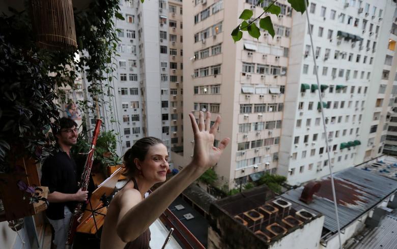 Музиканти класичної музики Софія Чеккато і її чоловік Симон Бечемін висловлюють подяку за те, що вони грають за сусідів зі свого балкона під час спалаху коронавирусной хвороби в Ріо-де-Жанейро, Бразилія, 21 березня 2020 року. REUTERS / Sergio Moraes