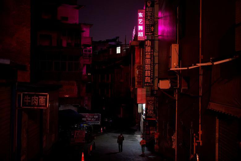 As pessoas usam máscaras faciais enquanto andam em uma comunidade residencial em Xianning, província de Hubei, China, 25 de março de 2020. REUTERS / Aly Song