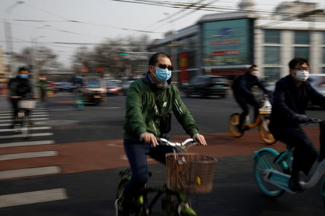 People wearing face masks ride bicycles on a street following an outbreak of the coronavirus disease (COVID-19), in Beijing, China March 30, 2020. REUTERS/Carlos Garcia Rawlins