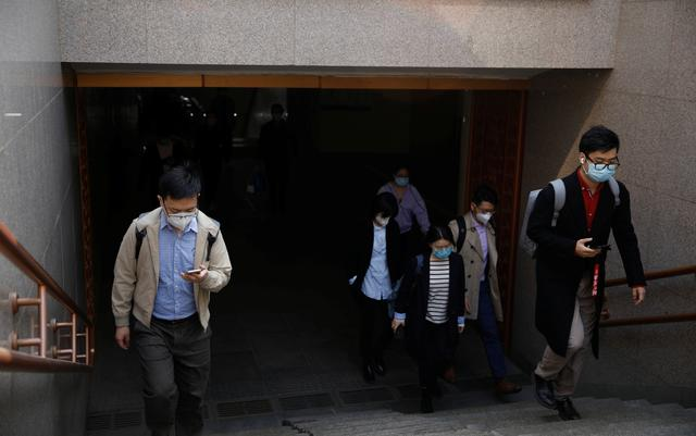 People wearing face masks exit a subway station following an outbreak of the coronavirus disease (COVID-19), in Beijing, China March 30, 2020. REUTERS/Carlos Garcia Rawlins