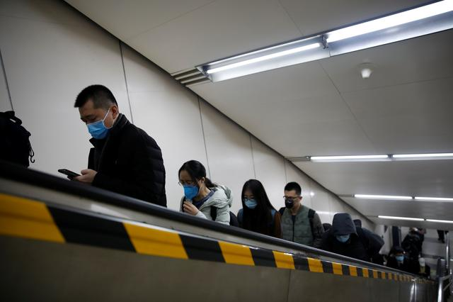 People wearing face masks ride an escalator as they exit a subway station following an outbreak of the coronavirus disease (COVID-19), in Beijing, China March 30, 2020. REUTERS/Carlos Garcia Rawlins