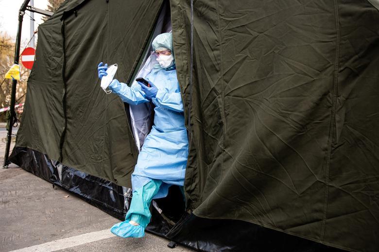 Врач в защитном костюме оставляет специальную палатку для случаев коронавирусной болезни возле больницы в Люблине, Польша, 23 марта 2020 года. Якуб Ожеховский / Agencja Gazeta via REUTERS