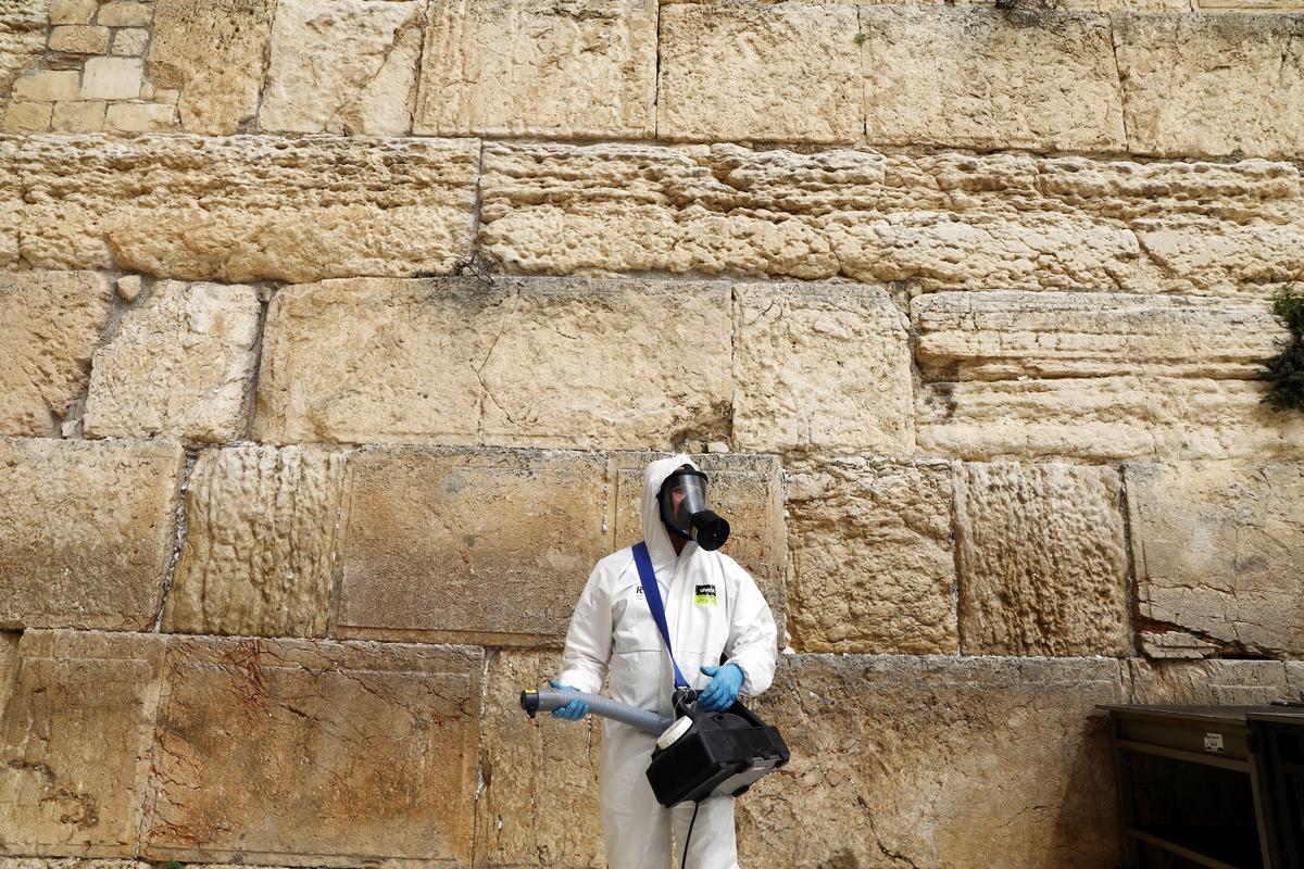 Workers in hazmat suits collect prayers from 'God's mailbox' in Jerusalem