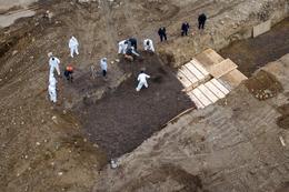 Workers bury the dead in mass grave on New York City's Hart Island amid coronavirus outbreak