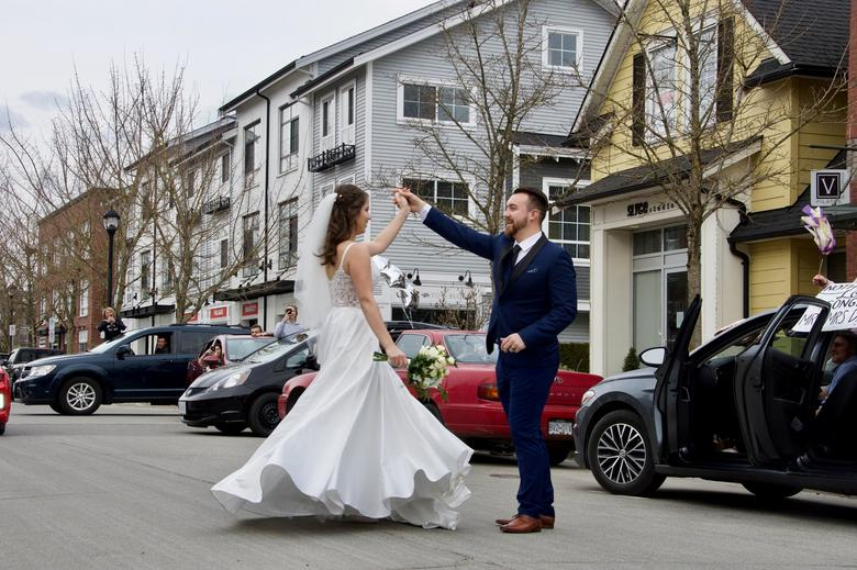 Joshua and Anastasija Davis dance to music their friends played from their cars at a surprise street party, after a living room wedding ceremony, as coronavirus-related social distancing restrictions altered their wedding plans, in Pitt Meadows, British Columbia, Canada March 22, 2020. Jan Frew via REUTERS