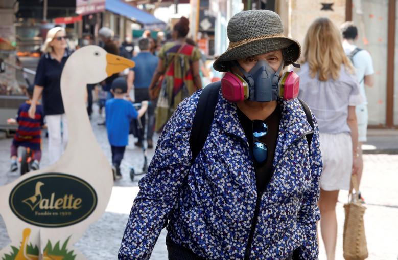 Жінка носить протигаз під час шопінгу в Парижі, Франція, 24 квітня 2020 року. REUTERS / Charles Platiau