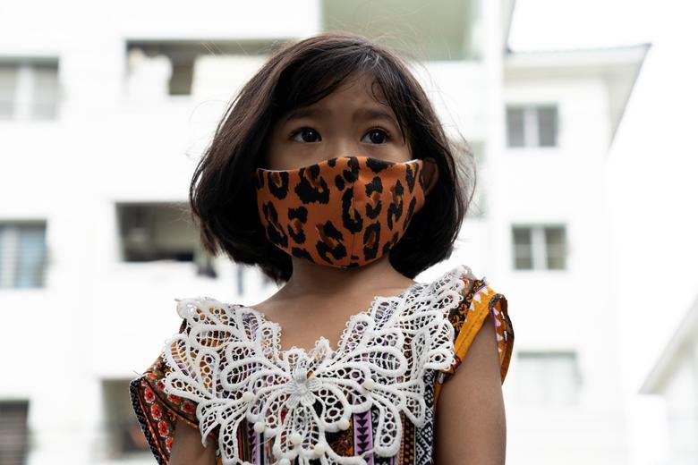 Дівчинка носить маску через спалах коронавирусной хвороби (COVID-19) в співтоваристві в Бангкоку, Таїланд, 10 квітня 2020 року. REUTERS / Athit Perawongmetha