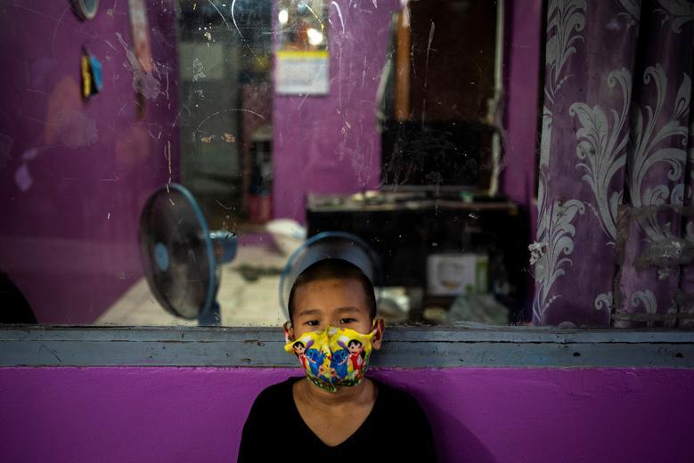 Хлопчик в масці дивиться на околицю Бангкока, Таїланд, 16 квітня 2020 року. REUTERS / Athit Perawongmetha