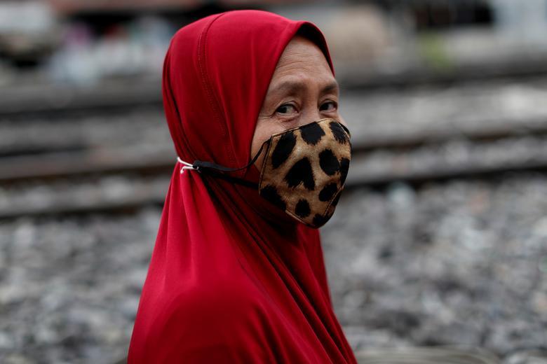 Мусульманка в захисній масці ходить поруч із залізничними коліями в Бангкоку, Таїланд, 27 квітня 2020 року. REUTERS / Jorge Silva