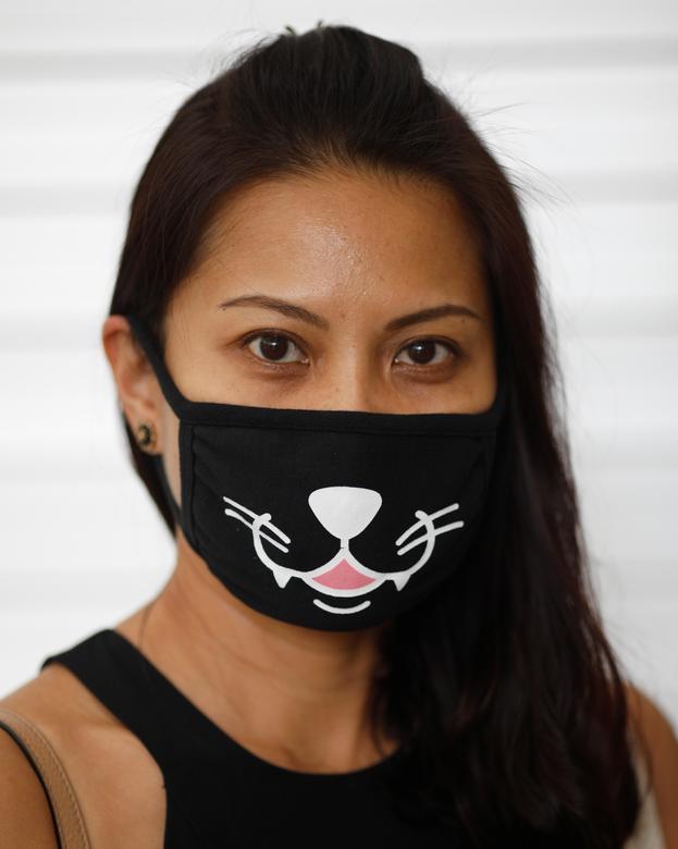 Жінка в масці позує для фотографії по дорозі в супермаркет в Сінгапурі, 15 квітня 2020 року. REUTERS / Edgar Su