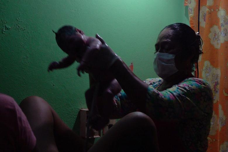Акушерка Хуаніта Зарат Солорз допомагає 29-річної Мариане народити її третьої дитини в місцевій клініці, а не в сусідній лікарні в Юніон Ідальго, Мексика, 19 квітня 2020 року. Зарат каже, що вона допомогла народити сотні дітей за 45 років, працюючи акушеркою в корінний громаді на півдні Мексики. Зараз попит на її послуги як ніколи високий, оскільки жінки намагаються не народжувати в лікарнях, де вони бояться заразитися швидко поширюється коронавірусів. Зарат сказала, що у неї заплановано чотири пологів на решту цього місяця і близько півдюжини в травні, в порівнянні з її звичайним показником від двох до трьох запланованих пологів на місяць. І все більше жінок можуть прибути в скрутну годину без попереднього запису. РЕЙТЕР / Хосе де Хесус Кортес
