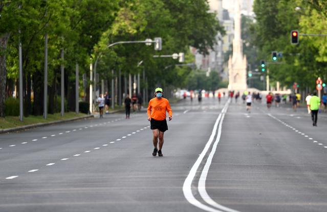 A man wearing a protective face mask jogs along Paseo de la Castellana avenue after Madrid's local authorities allowed some streets only for pedestrian use during weekends and festivity days amid the coronavirus disease (COVID-19) outbreak in Madrid, Spain, May 9, 2020. REUTERS/Sergio Perez