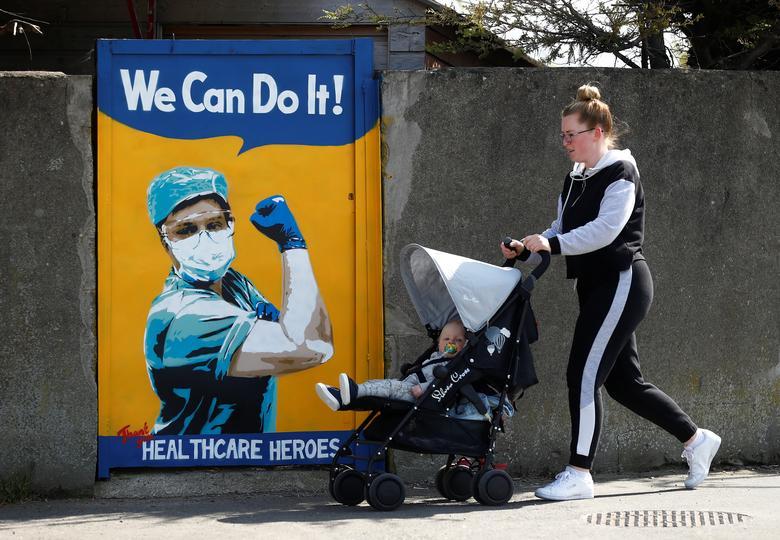 Женщина толкает ребенка в багги возле фрески Эммы Блейк в Дублине, Ирландия, 21 апреля. РЕЙТЕР / Джейсон Кэрндафф