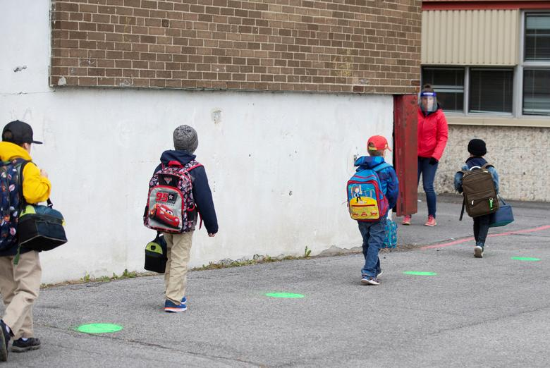 Зеленые точки помещены на школьном дворе, чтобы помочь ученикам продолжать дистанцироваться в Сен-Жан-сюр-Ришелье, Квебек, Канада, 11 мая. РЕЙТЕР / Кристин Муски
