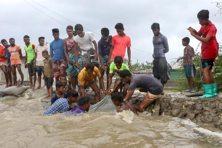 Местные жители пытаются укрепить насыпь до того, как циклон Амфан обрушится на берег в Габуре на окраине района Сатхира, Бангладеш, 20 мая. РЕЙТЕР / Стрингер