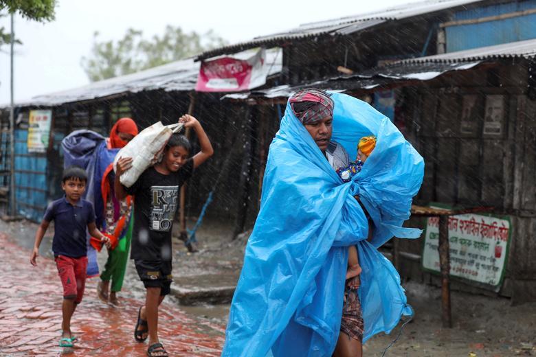 Люди добираются до более безопасного места, прежде чем Циклон Амфан обрушится на берег в Габуре, на окраине района Сатхира, Бангладеш, 20 мая. РЕЙТЕР / Стрингер