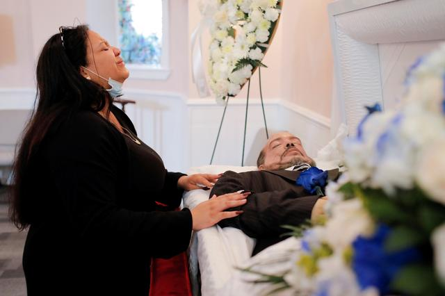 Jessica Holguin, 25, reacts as she kneels beside the body of her father Jose Holguin, 50, originally from the Dominican Republic and who died of complications related to the coronavirus disease (COVID-19) during a viewing service held for him at International Funeral & Cremation Services in the Harlem neighborhood of Manhattan, New York City, U.S., May 16, 2020. Picture taken May 16, 2020. REUTERS/Andrew Kelly