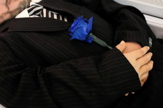 A blue rose is seen placed in the hands Jose Holguin, 50, originally from the Dominican Republic and who died of complications related to the coronavirus disease (COVID-19), during his viewing service at International Funeral & Cremation Services in the Harlem neighborhood of Manhattan, New York City, U.S., May 16, 2020. Picture taken May 16, 2020. REUTERS/Andrew Kelly