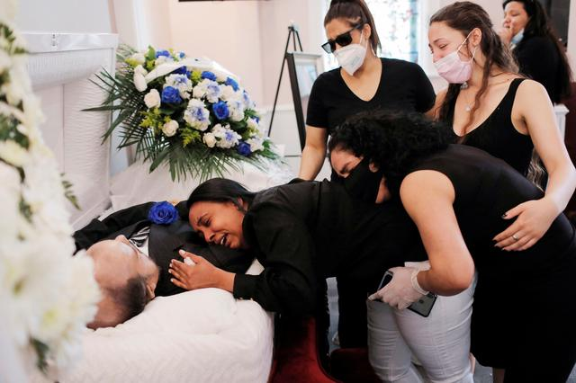 Maria Ortiz embraces the body of her partner Jose Holguin, 50, originally from the Dominican Republic and who died of complications related to the coronavirus disease (COVID-19), while she is supported by Mr. Holguin's family during his viewing service at International Funeral & Cremation Services in the Harlem neighborhood of Manhattan, New York City, U.S., May 16, 2020. Picture Taken May 16, 2020. REUTERS/Andrew Kelly