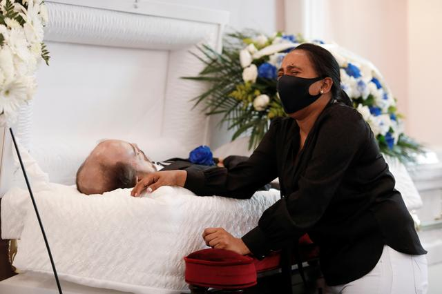 Maria Ortiz reacts while kneeling beside the body of her partner Jose Holguin, 50, originally from the Dominican Republic and who died of complications related to the coronavirus disease (COVID-19), during a viewing service for Mr. Holguin at International Funeral & Cremation Services in the Harlem neighborhood of Manhattan, New York City, U.S., May 16, 2020. Picture taken May 16, 2020. REUTERS/Andrew Kelly