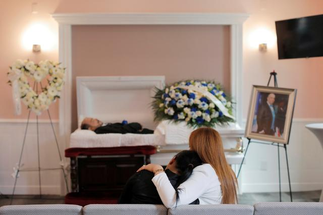 Maria Ortiz (L) is comforted as she looks toward the body of her partner Jose Holguin, 50, originally from the Dominican Republic and who died of complications related to coronavirus disease (COVID-19), during a viewing service for Mr. Holguin at International Funeral & Cremation Services in the Harlem neighborhood of Manhattan, New York City, U.S., May 16, 2020. Picture taken May 16, 2020. REUTERS/Andrew Kelly